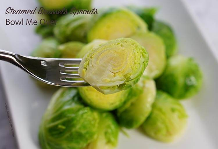 Steamed brussels sprouts on plate with fork.