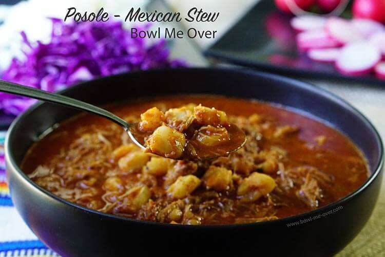 A black bowl filled with posole Mexican stew