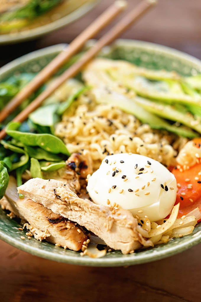 Green bowl filled with Ramen Noodles, chicken, bok choy, carrots and spinach topped with toasted sesame seeds