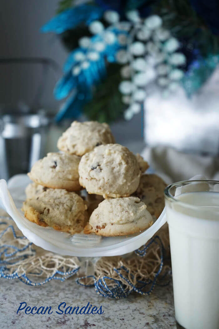 A white bowl full of Homemade Pecan Sandies with a glass of milk ready to dunk cookies into. This pecan sandies recipe was my Grandma's and these cookies are delicious!