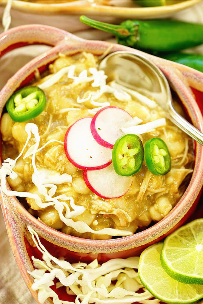 Chicken Posole Recipe in a bowl topped with jalapeños, radishes and cabbage.