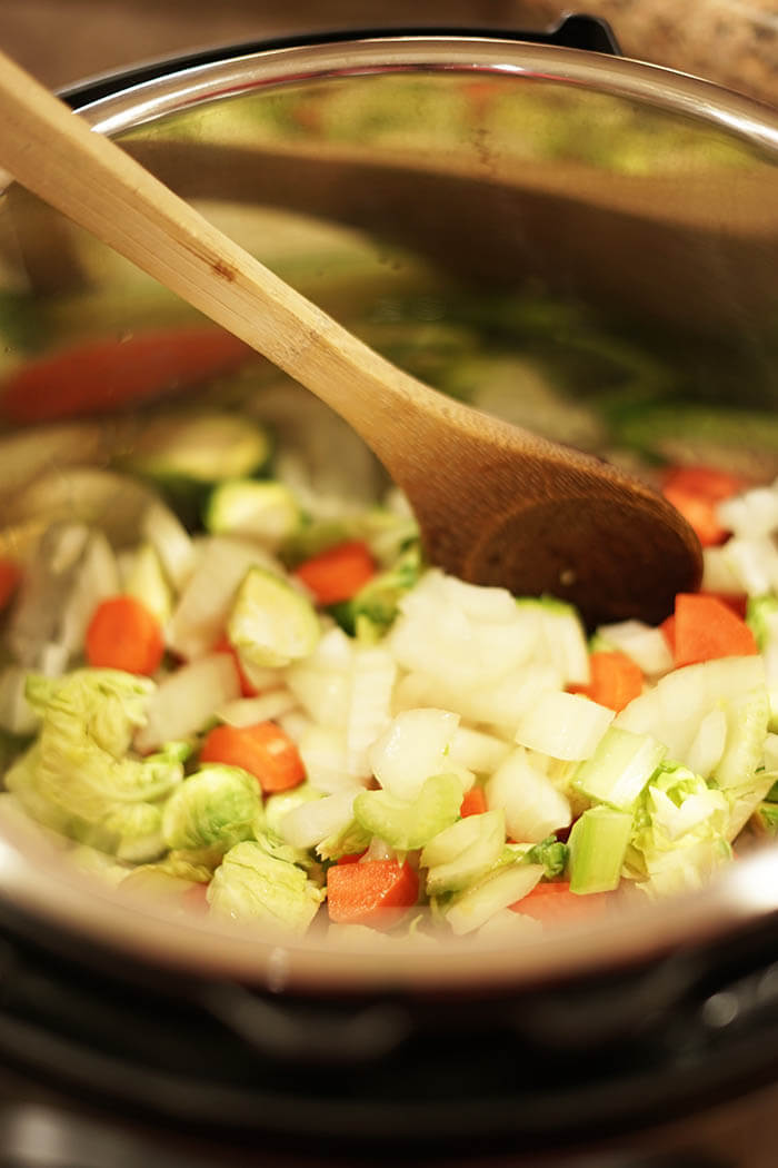 A picture of the inside of an Instant Pot. There are carrots, onions, and brussels sprouts sautéing and a wooden spoon stirring the vegetables.