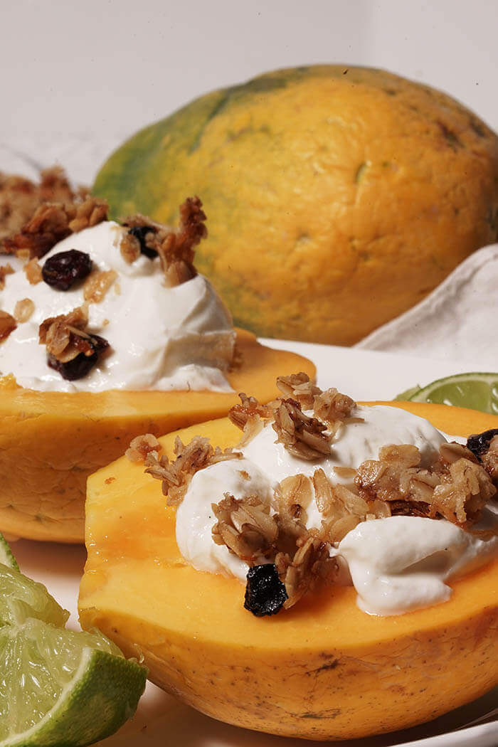 A ripe juicy papaya that's been sliced in half. The seeds have been scooped out and a dollop of thick greek yogurt fills the center. The yogurt is topped with granola and a squeeze of lime to make a delicious breakfast bowl. More lime wedges surround the papaya and a whole papaya is in the background.