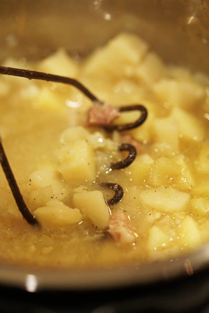 An old fashioned metal potato masher, mashing the cooked potatoes making the soup thick and creamy.