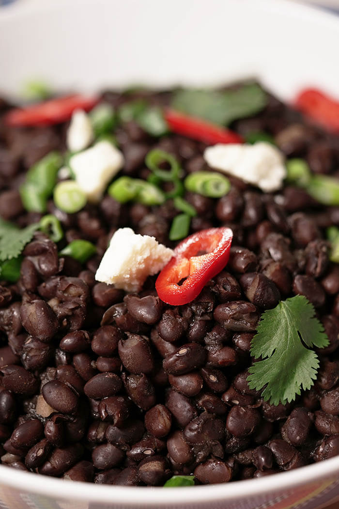 Cook Black Beans topped with cheese, cilantro and red jalapeños.