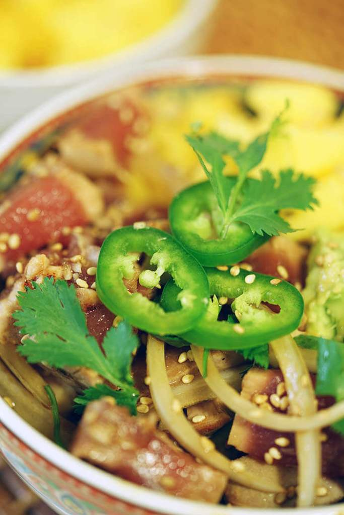 Bowl topped with with seared tuna, mango, avocado topped with sliced jalapeños and cilantro.