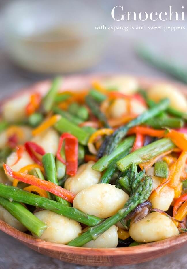 A bowl full of gnocchi pasta, sweet asparagus with red and orange bell peppers. This is a bright fresh vegan meal.