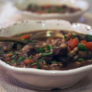 A white bowl filled to the brim with a hearty beef barley soup recipe.