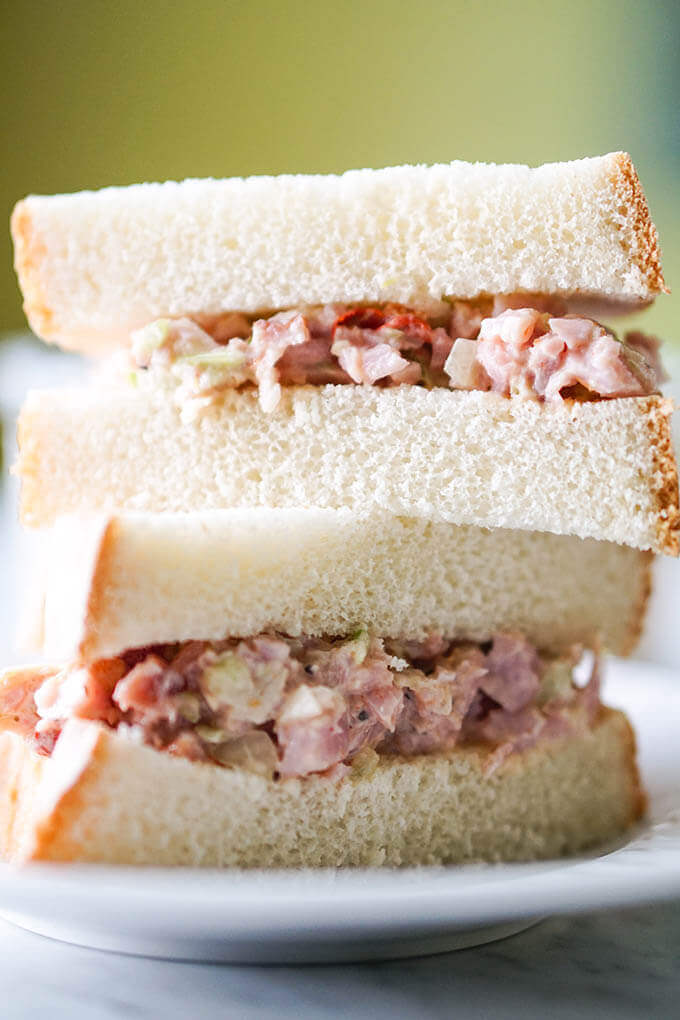 A sandwich made with ham spread on white bread. The sandwich is sliced in half and stacked up.