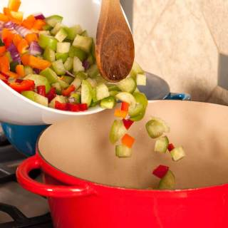 A rainbow of vegetables being spooned into a red stock pot.