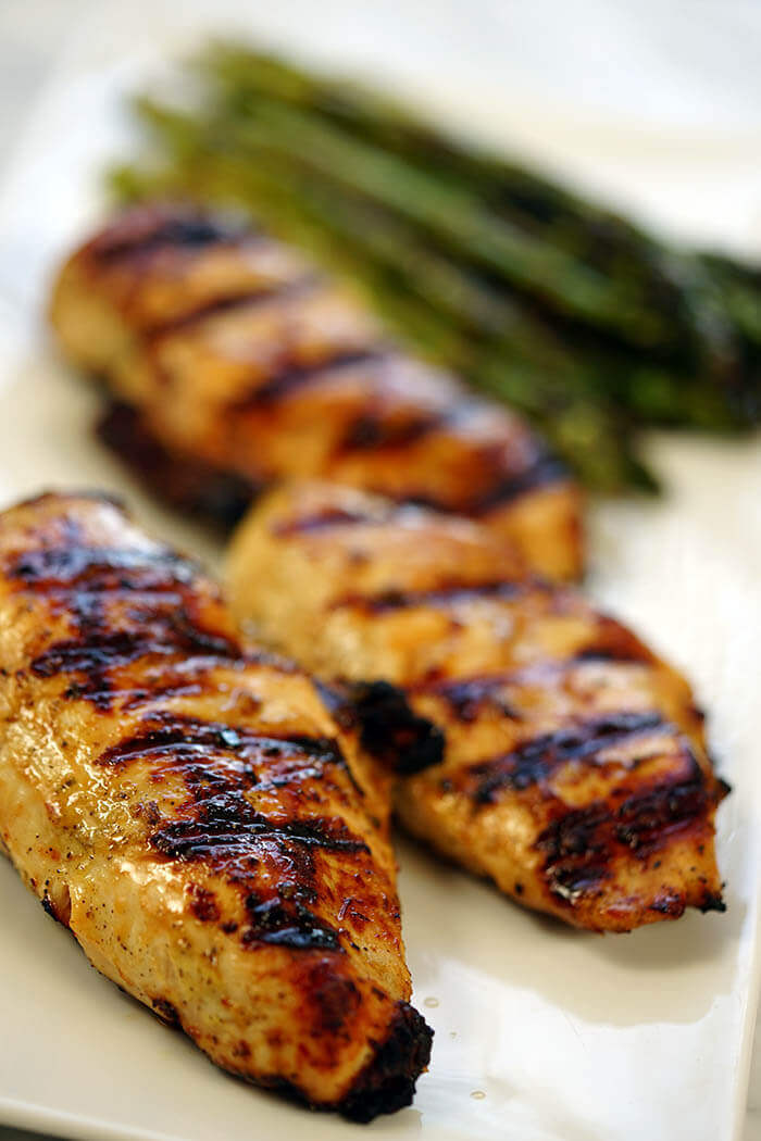 Lemon pepper marinade grilled chicken breasts on a white plate with some grilled asparagus.