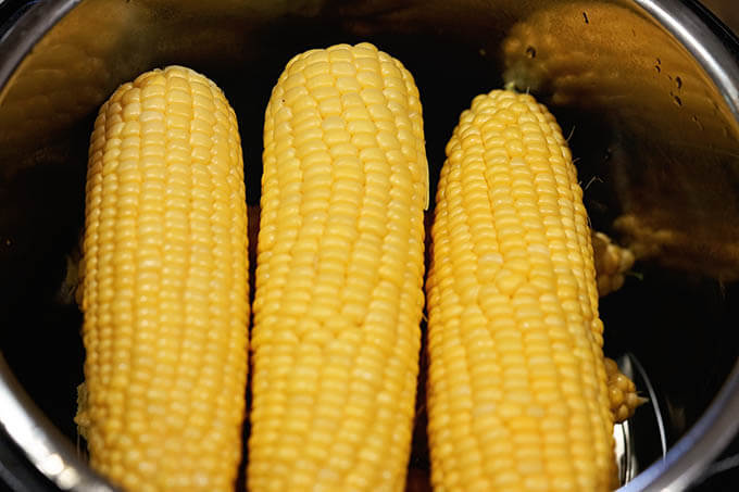 Corn stacked in the pressure cooker ready to be cooked. This method is an Instant Pot Corn on the Cob recipe.
