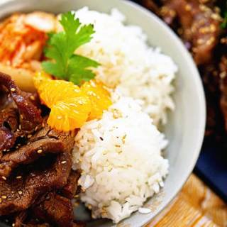 Korean BBQ Beef Bowl with beef, rice and kimchi., garnished with sliced mandarins.
