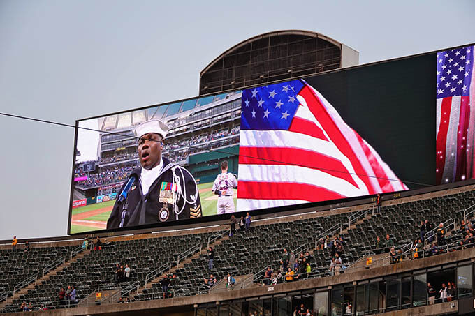 A picture of the megatron and a sailor from the United States Navy singing the National Anthem with a United States Flag flying high.