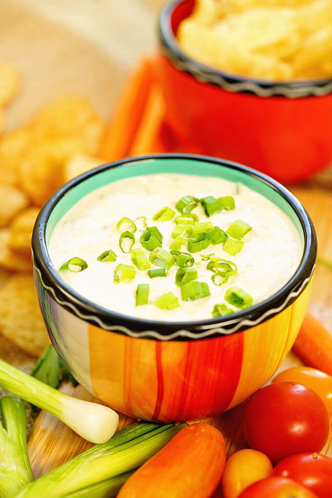Green Onion Dip Recipe surrounded by dippers like potato chips, cherry tomatoes, carrots and green onions.
