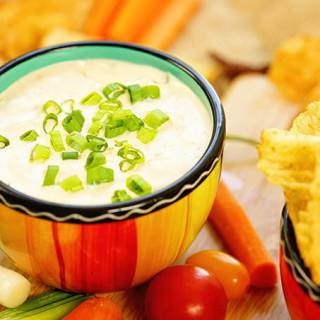 Onion Dip in a color ful surrounded by chips and veggies for dipping.