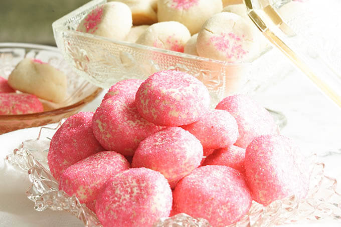 Pink cookies on glass platter.