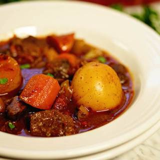 Stew in white bowl. The stew is full of tender lamb morsels and big chunky vegetables.