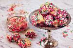 Homemade Shortbread cookies on a silver platter on a marble board surround by piles of sprinkles!