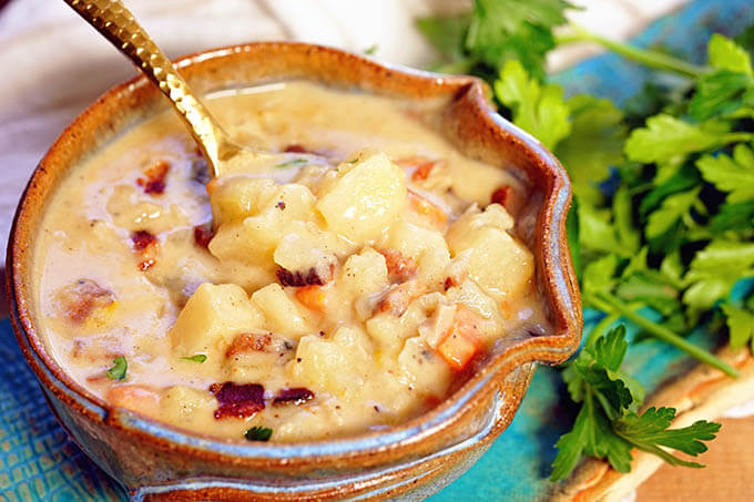 A blue bowl filled with the best clam chowder topped with crumbled bacon.