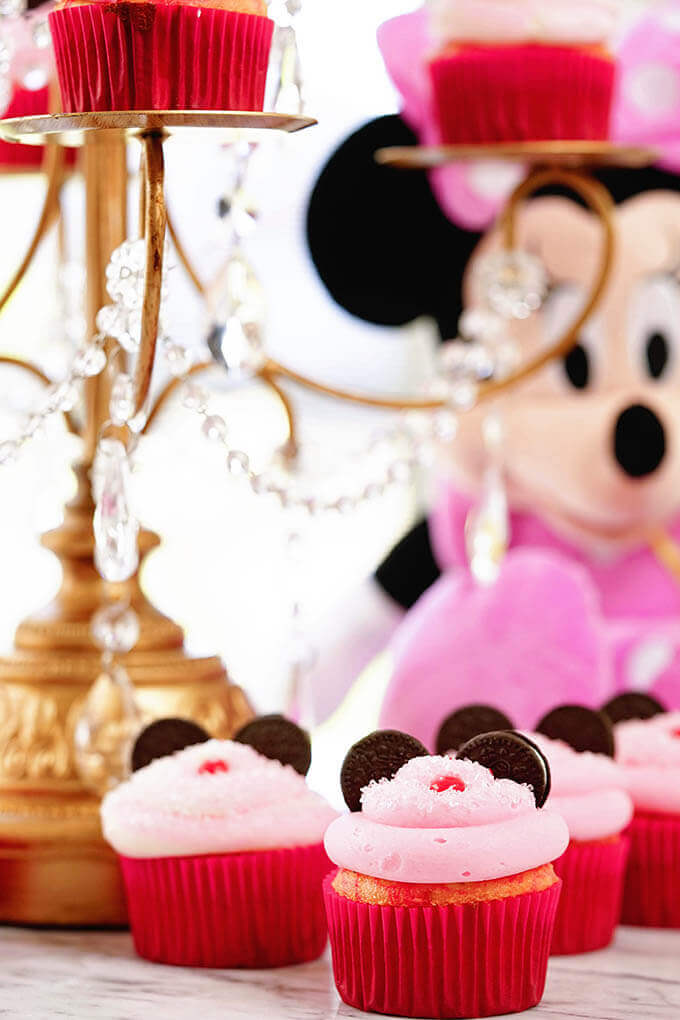 Minnie Mouse cupcakes surrounding a cake stand and stuffed Minnie Mouse!