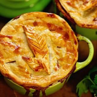 Turkey Pot Pie in green ramekins baked with a golden crust.