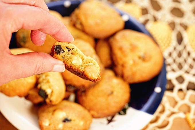 A hand holding a cookie filled with figs, macadamia nuts and white chocolate chips.