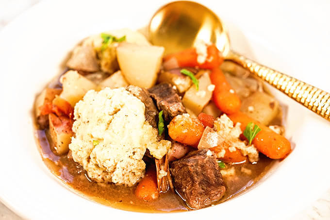 Easy Crockpot Beef Stew in a white bowl with spoon.