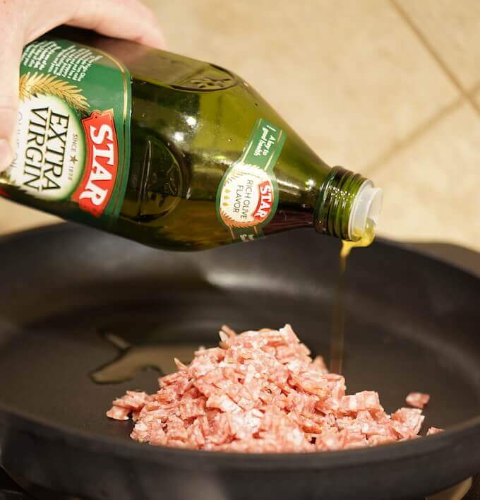Minced salami in a cast iron pan. It is being fried with Extra Virgin Olive Oil