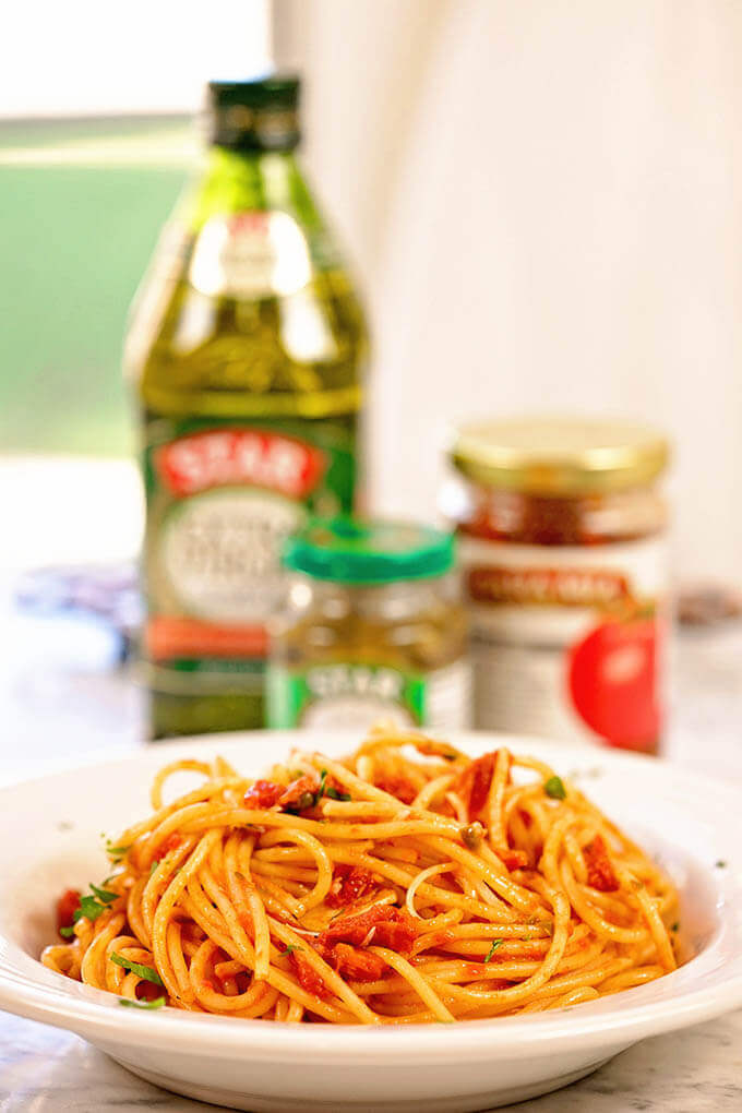 Spaghetti Puttanesca in a white bowl.