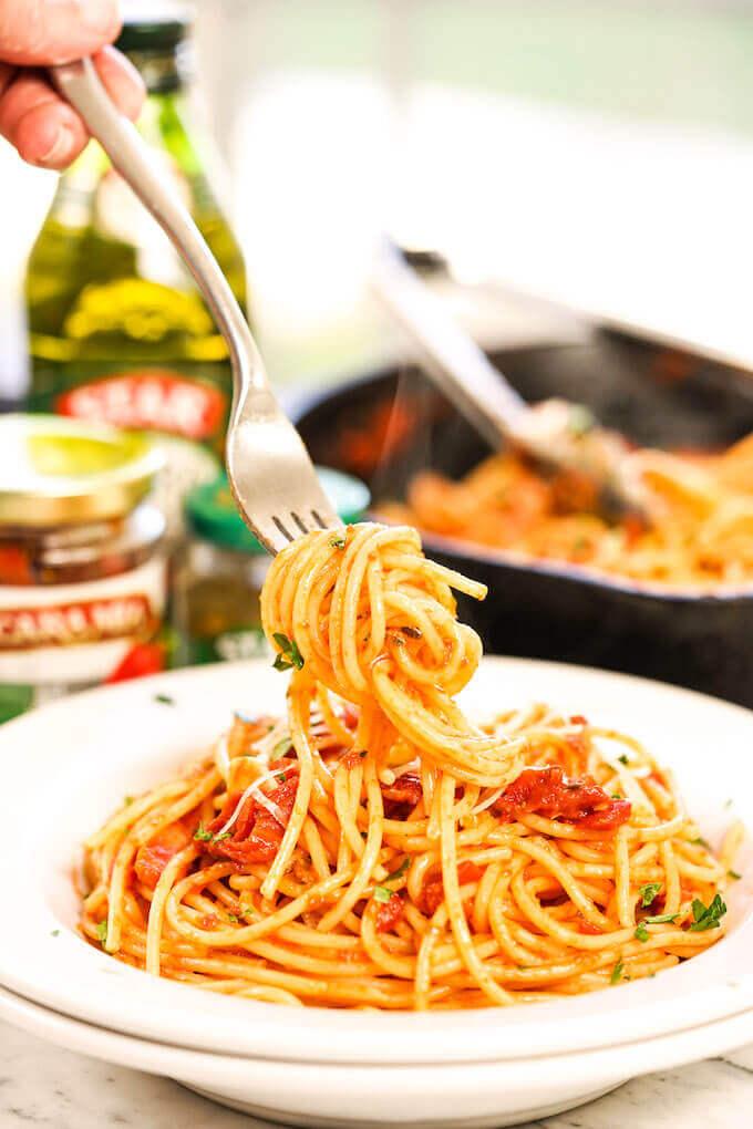 Pasta Puttanesca in white bowl with spaghetti twirled around fork..