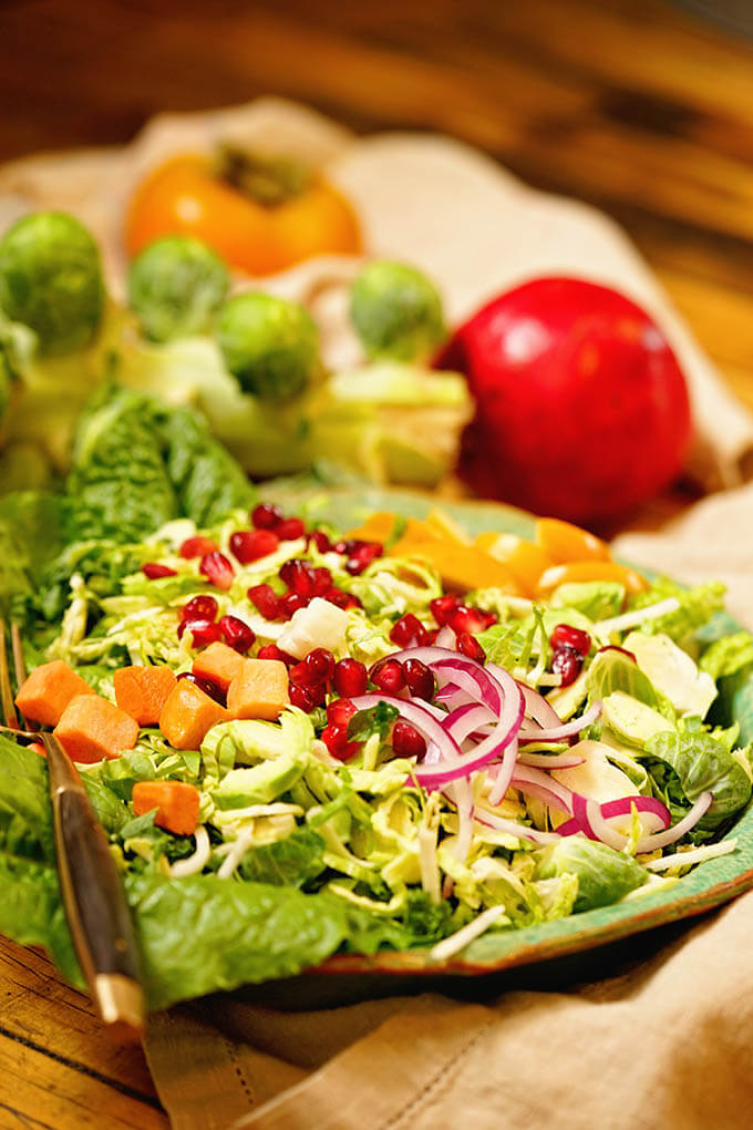 Shaved Brussel Sprout Salad in green bowl topped with pomegranate arils and sliced peaches