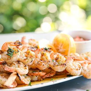 Easy Grilled Shrimp Skewers on platter with lemons and cocktail sauce.