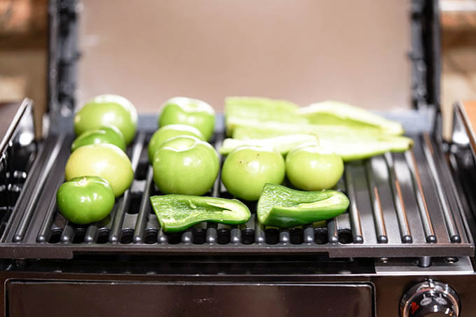 Tomatillos, peppers and jalapeños roasting on grill.