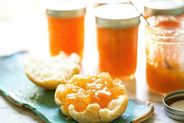 Jam on muffin on blue platter.