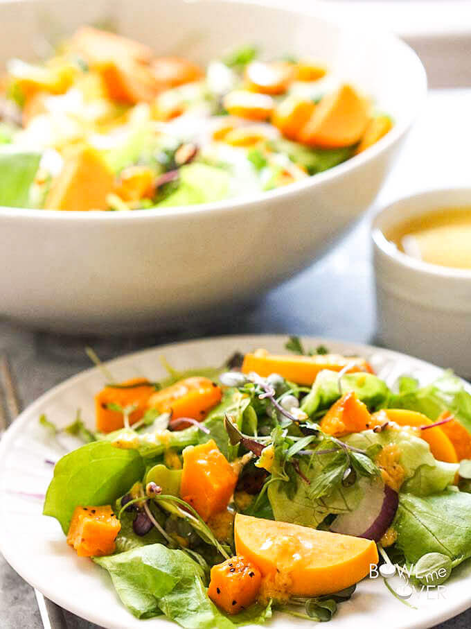 Fall Harvest Salad on white plate with salad dressing on the side