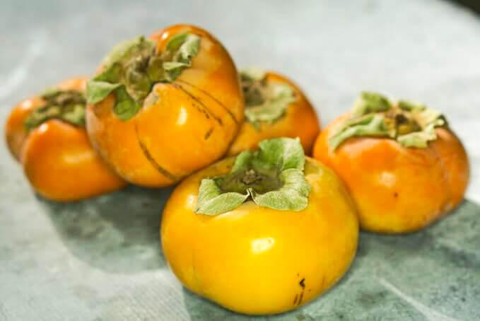 Orange persimmons on a metal countertop.