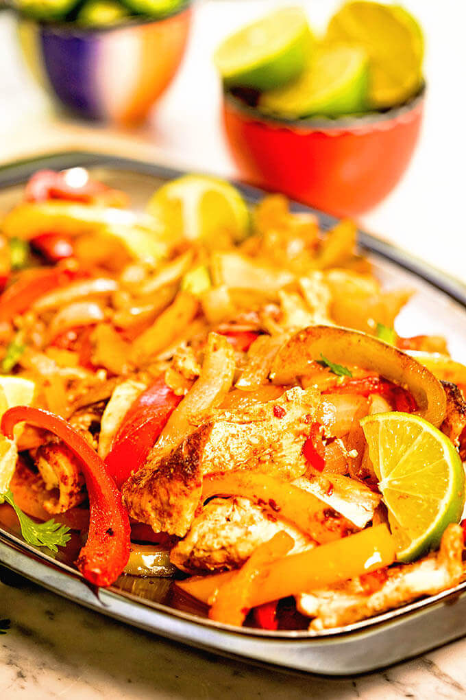 Oven baked fajitas on platter with lime