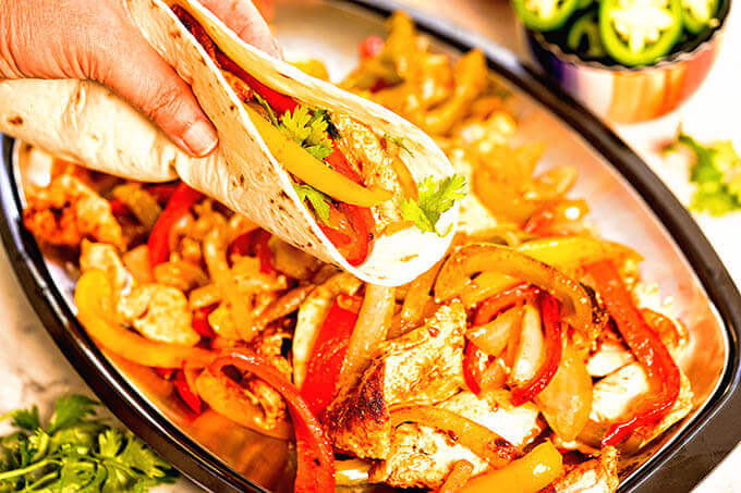 Hand holding flour tortilla shell filled with chicken, peppers and onion.