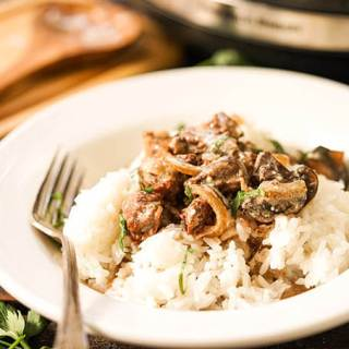 Easy Crock Pot Beef Stroganoff in white bowl with fork.