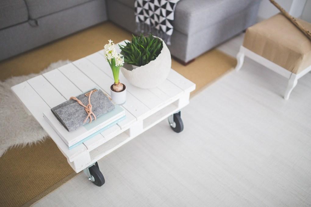 sol en parquet clair tapis marron et plaid géométrique avec table en palette