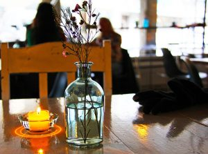 Bouteille en verre comme vase et bougie chauffe-plat sur une table en bois