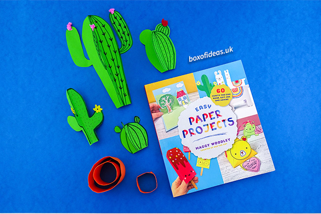 Resting 3-d cactus crafts next to the book 60 easy paper projects #papercraft #kidscraft #craftsforkids #cactus #easycrafts #boxofideas
