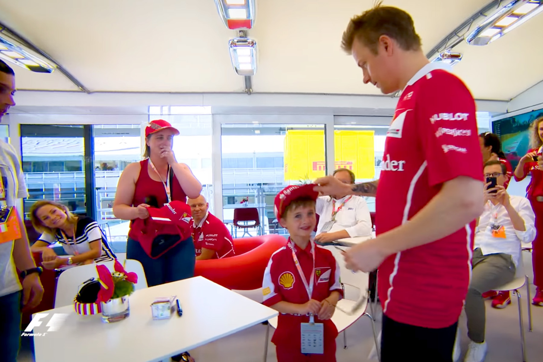 Ferrari's Kimi Raikkonen gives an autographed cap to a young fan