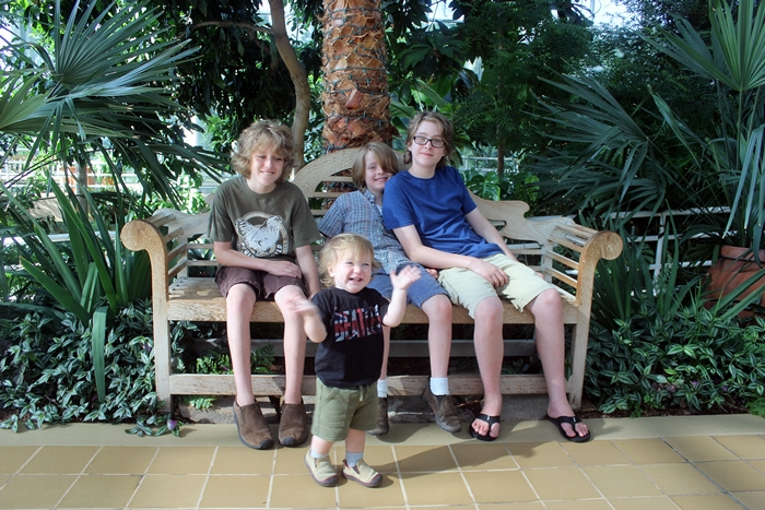 four kids in front of plants