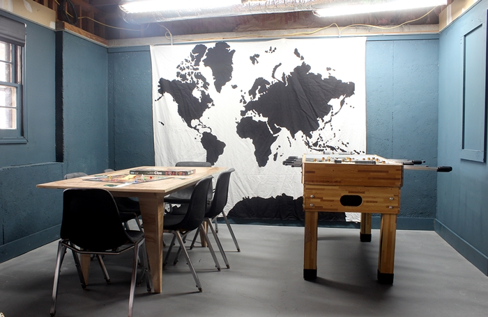 basement room with plywood game table, foosball table, and Urban Outfitters map tapestry