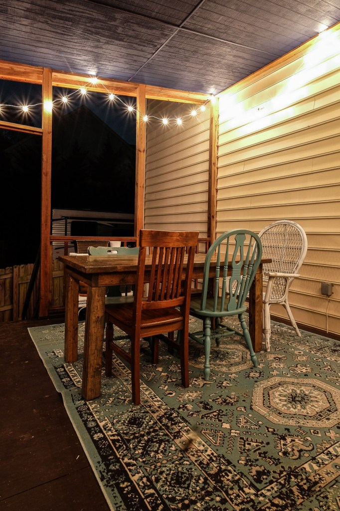 navy stain and string lights on a covered porch