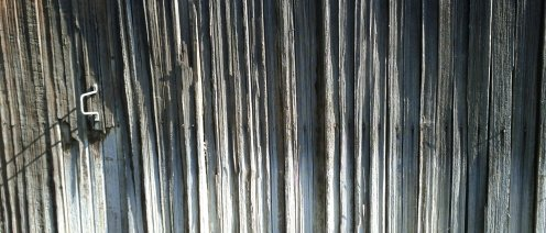 Sun bleached patterns on a split rail fence.