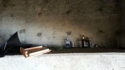 Growing altar of liquor bottles.