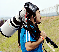 Photographer with large Canon lens and camera